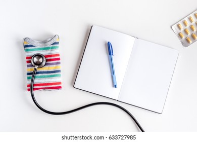 Pediatrician workplace with stethoscope and notebook on white background top view mockup