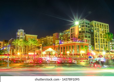Pedicabs lighting, cars and metro line stop at level crossing in Harbor Drive between Marina district and Gaslamp Quarter in San Diego Downtown, California, USA. Light trails effect by night.