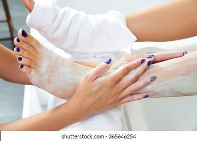 Pedicure aplying nourishing moisturizer mask in legs of woman in nails salon
