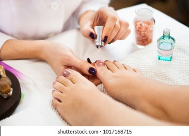 Pedicure in beauty spa salon. Beautician polishing nails. Foot care treatment and nail, the woman at the beautician for pedicure. Close up.