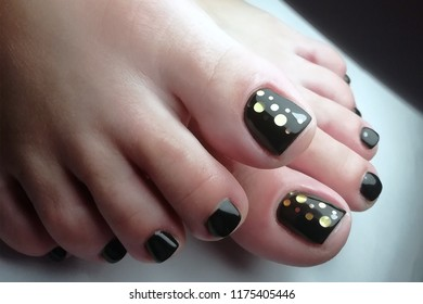 pedicure of the foot close-up black lacquer with sequins, beauty salon