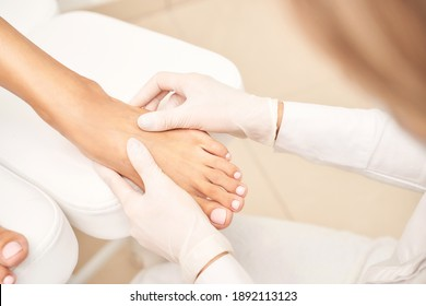 Pedicure nail spa procedure. Foot manicure. Salon master. Polish woman leg. Hands in gloves. Light background. Massage service. Healthy toe cleaning. Pink pastel color. Dermatology cream