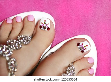 Pedicure on women's legs covered with white and pink varnish with rhinestones on the pink background.
