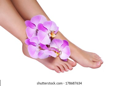 Pedicure with pink orchid flowers isolated on white. Beautiful female feet with french manicure. Foot care. Spa
