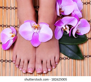 Pedicure with pink orchid flowers on bamboo mat. Beautiful female feet with french manicure. Foot care. Spa