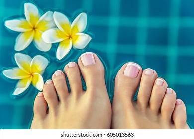 pedicure woman's feet at spa near jasmine flowers