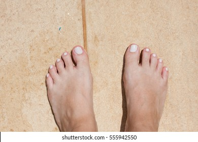 Pedicured two feet on beige rocky floor