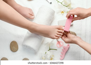 Pedicurist buffing toe nails. Woman's foot on a white towel roll. Nice service of beauty procedures.