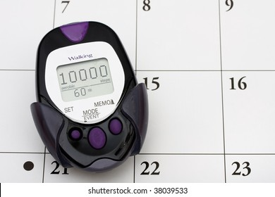 A pedometer with 10000 steps on it on calendar background, important date