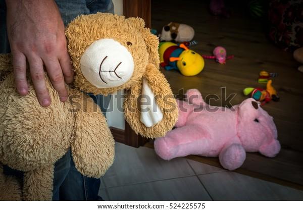 Un pédophile avec un jouet câlin essayant de voler un enfant - concept d'enlèvement