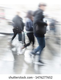 Pedople in blurred motion rushing over pedestrian crossing on rainy day