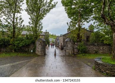 PEDRAFITA DEL CEBRERO, SPAIN - JUN 13, 2017: Tourists and pilgrims on the street of the town in the rain