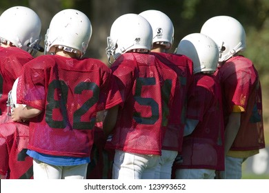 Pee Wee football players in a huddle with red uniforms and white helmets