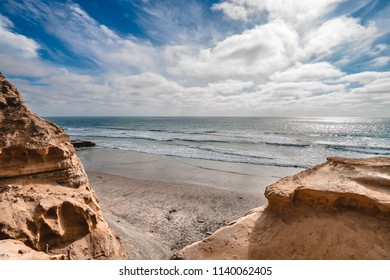 A peek between sandstone cliffs over the pacific ocean of white clouds meeting the end of the earth across the horizon.