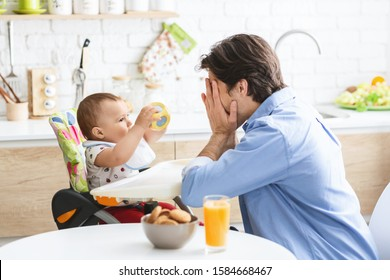 Peekaboo. Cheerful daddy playing with cute baby son in kitchen interior, empty space