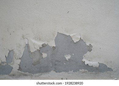 Peel off paint on concrete walls with old peeling paint. Rough painted surfaces, weathering, patterns of cracks and stripping.