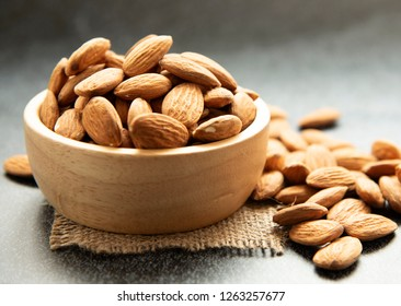 Peeled almonds in bowl wooden on dark background.