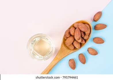 Peeled almonds seeds with almond oil on color paper background with empty space for your text or message.
