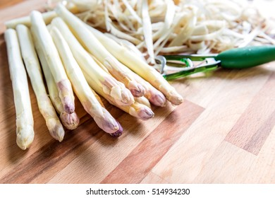 Peeled asparagus, ready for prepared is on the wooden background with peeler