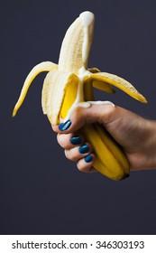 peeled banana ejaculates with yogurt in female hand