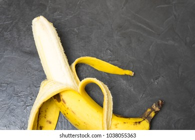 Peeled banana on a black background. Place for your text...