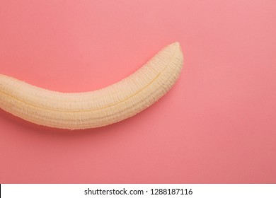 Peeled banana on pink background, penis erection metaphor