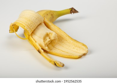 A peeled and bitten banana in a peel on a white background. Old one peeled banana. Tropical yellow fruit. Selective focus. Bitten Banana.