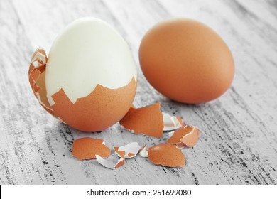 Peeled boiled egg on wooden background