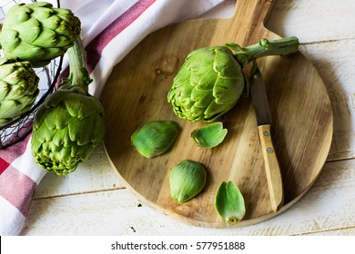 Peeled fresh artichoke preparing for cooking, wood cutting board, knife, vegetables in metal basket, rustic kitchen interior, top view