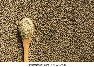 Peeled hemp kernels in wooden spoon on background of organic kernels and seeds. View from above. Space for text.