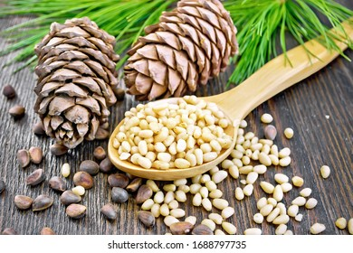 Peeled kernels of cedar nuts in a spoon, two pine cones, green branches and nuts in the shell against a dark wooden board