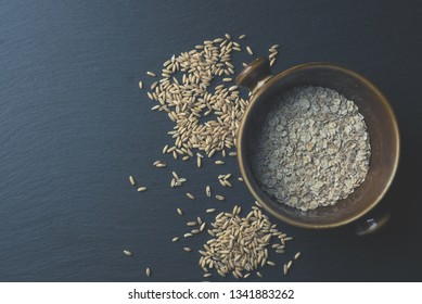 Peeled oats and oat meal on a dark stone table, healthy food concept, view from above