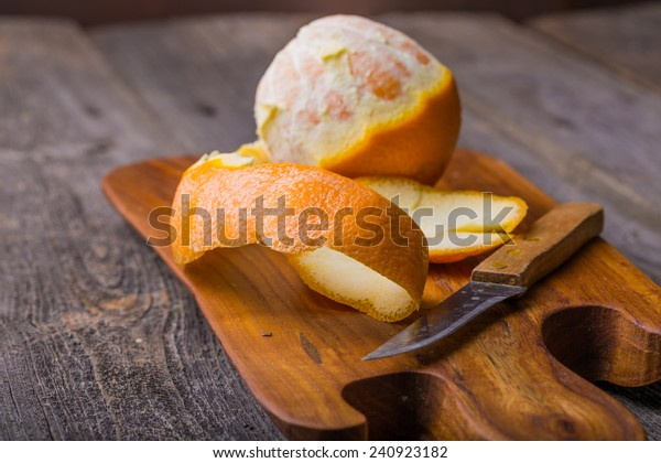 Peeled orange on wooden cutting board