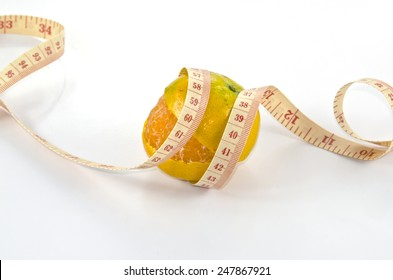 Peeled orange wraped with measuring tape for diet