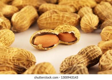 Peeled peanuts on well peanuts in background. Macro image