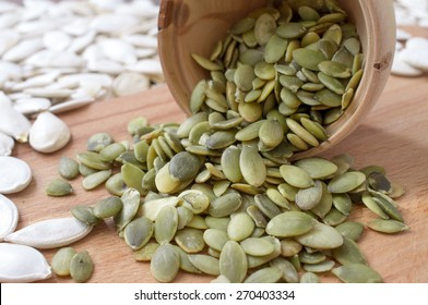 Peeled pumpkin seeds pour from a wooden cup