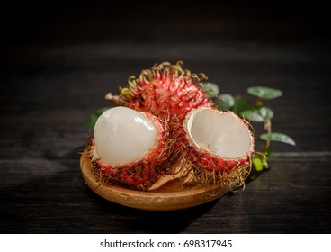 peeled rambutan fruits with vanilla on wooden plate isolated on black background
