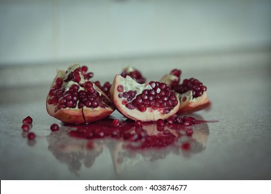 Peeled red ripe pomegranate on a reflective surface.