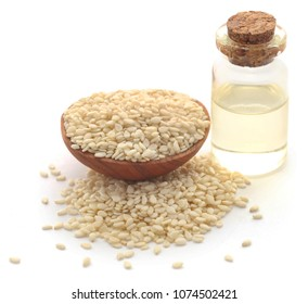 Peeled sesame seeds with oil in a bottle over white background