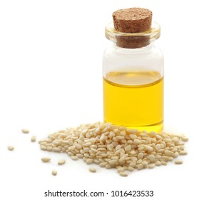 Peeled sesame seeds with oil in a small jar over white background