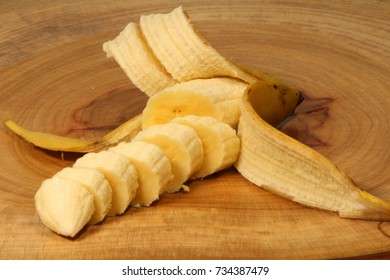 A peeled and sliced banana lying on a wooden cutting board in a kitchen.