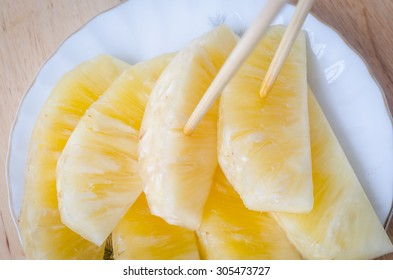 Peeled and sliced pineapples in a white dish on wooden table