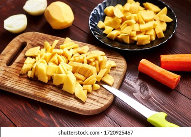 peeled sliced raw potatoes on a wooden board. Preparing vegetables for cooking.