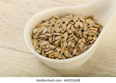 Peeled sunflower seeds heap over the wooden background