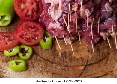 Peeled tomatoes, peppers, beef sticks on a wooden board