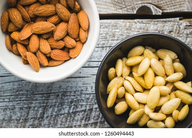 Peeled and unpeeled almonds in bowl. Top view.