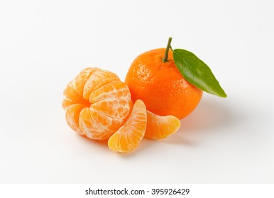 peeled and unpeeled tangerines on white background