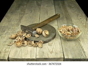 peeled walnuts, a hammer and a wooden table