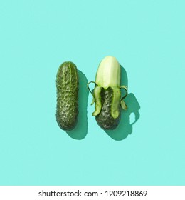 Peeled and whole cucumbers on a blue background with reflection of shadows and copy space for text. Healthy Diet Food. Top view