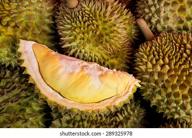 Peeled yellow Mon Thong durian on heap of durian fruits